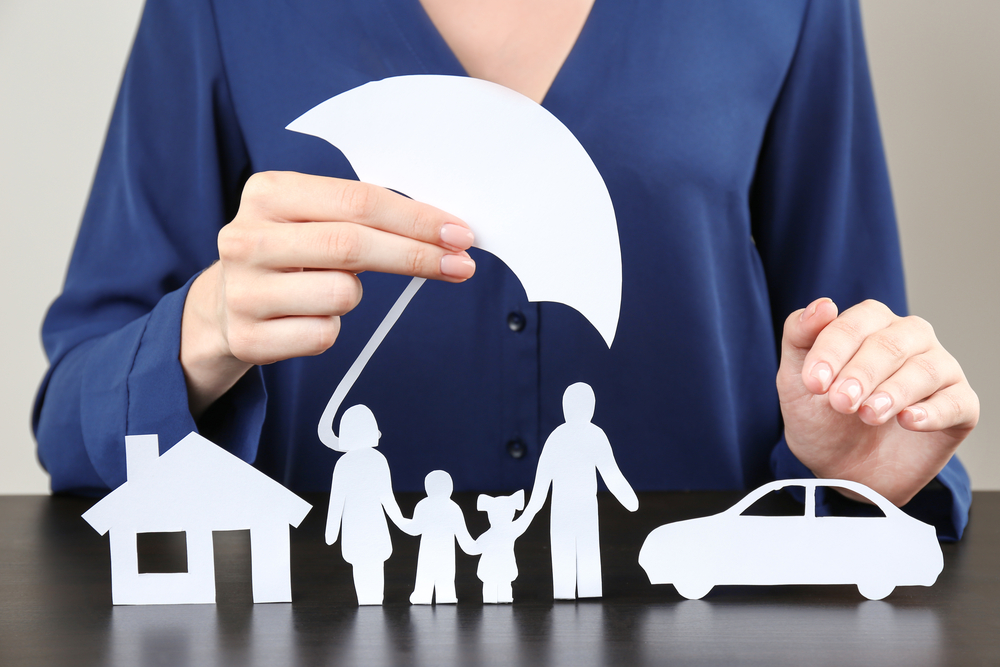 image of umbrella over a home, car and people